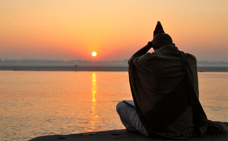 A devotee praying the rising Sun at famous Varanasi ghats